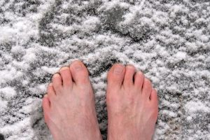 photo of man with bare feet standing in snow